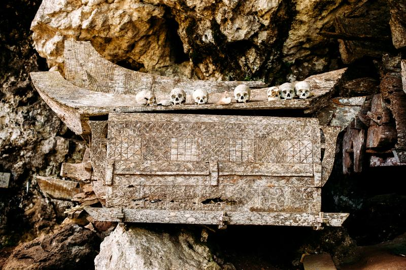 Old wooden coffin with skulls and bones nearby on a rock. Hanging coffins, graves. Traditional burials site, cemetery Kete Kesu in. Rantepao, Tana Toraja stock image