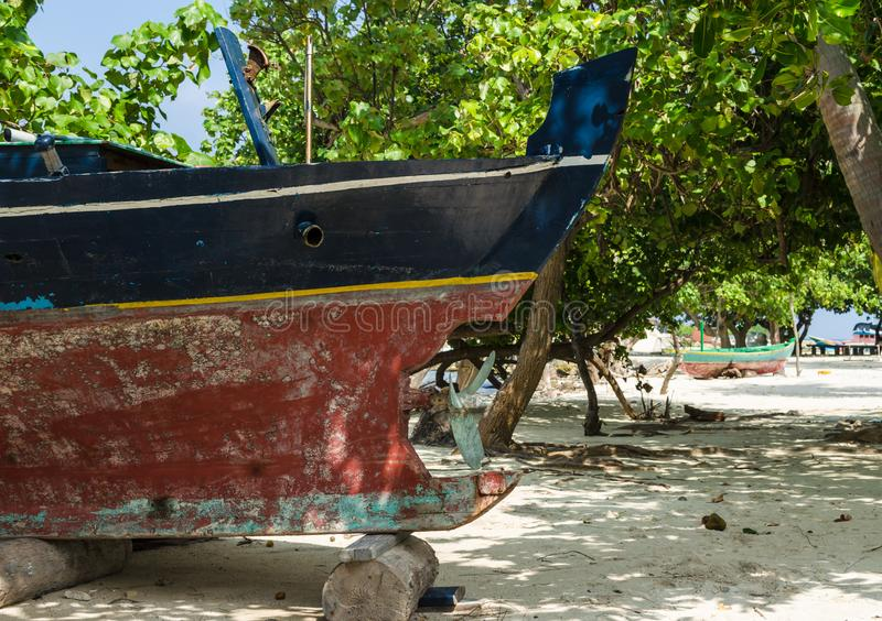 Old wooden colorful boat on the white sand of the tropical island. Maldives, wild paradise stock images