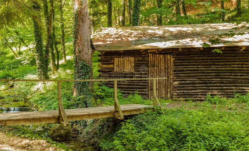 Old wooden cottage next to a stream in Sokobanja, Serbia. Beautiful nature scenery stock photo