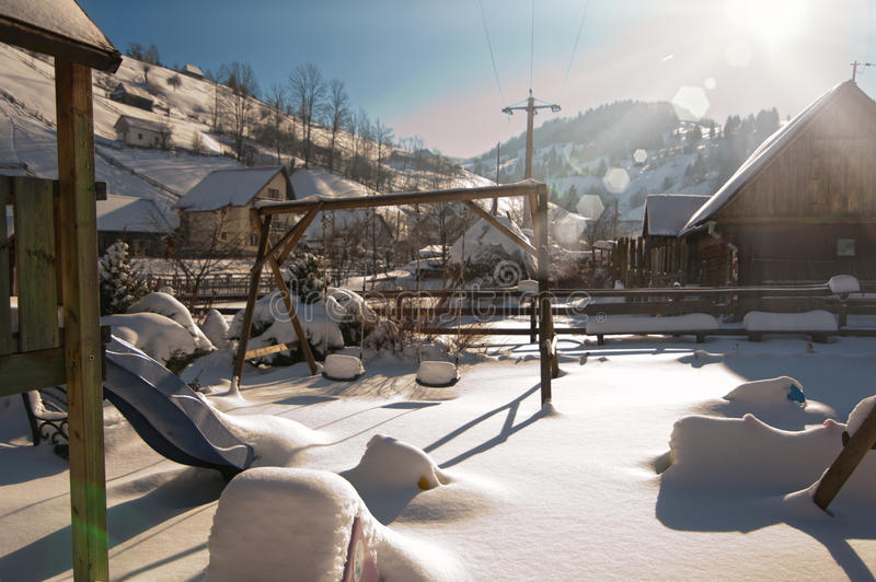 Old wooden cottages and wooden Romanian swings covered by snow. Cold winter day at countryside. Traditional Carpathian mountains royalty free stock photography