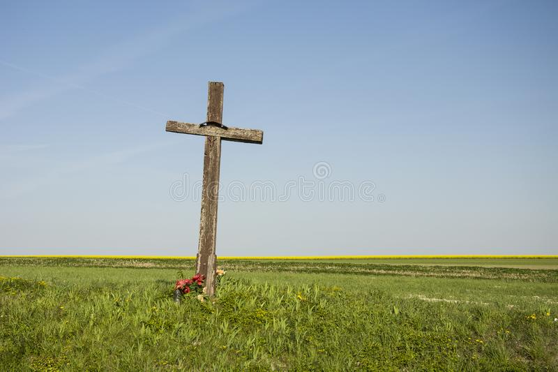 Old wooden cross on the field. Old wooden cross on the green field stock image