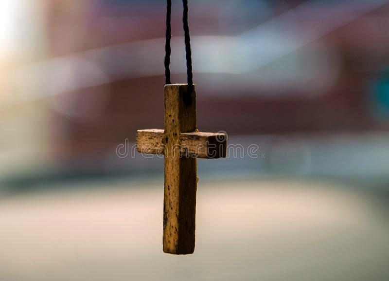 Old wooden cross on a thread stock image