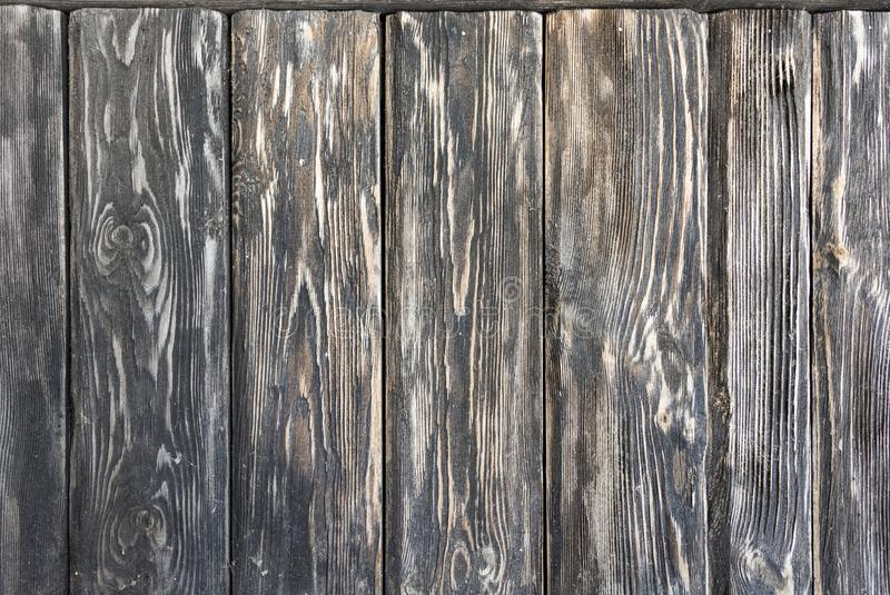 Old wooden dark background consisting of shabby black-brown textured boards. stock photos