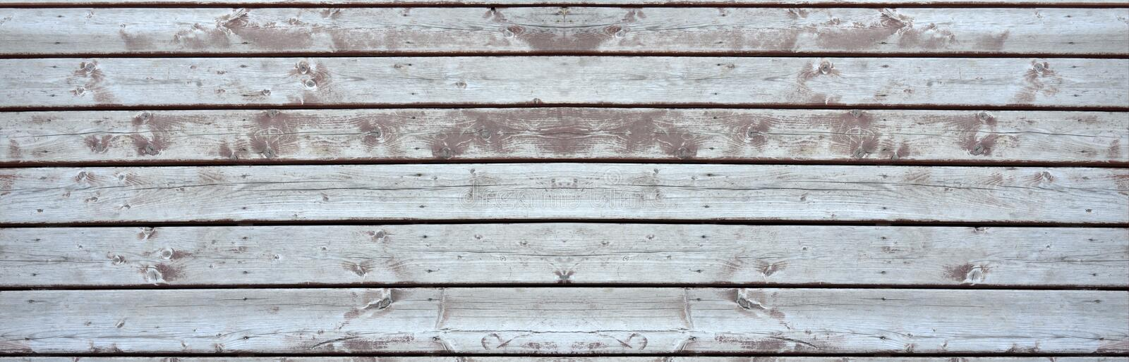Old wooden deck elongated. Old wooden deck in need of repair and renovation - elongated royalty free stock photos