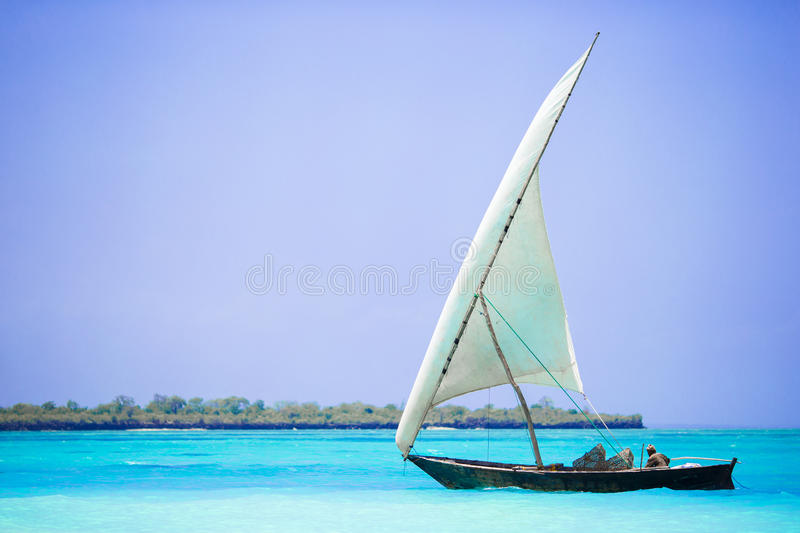 Old wooden dhow in the Indian Ocean near Zanzibar. Small wooden boat in stunning turquoise water stock photos