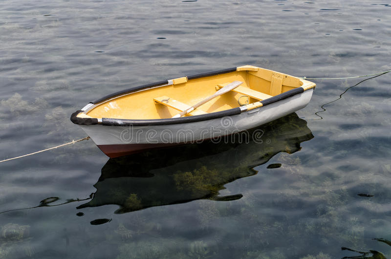 Old wooden dinghy. View of old wooden dinghy tied to the pier royalty free stock photos