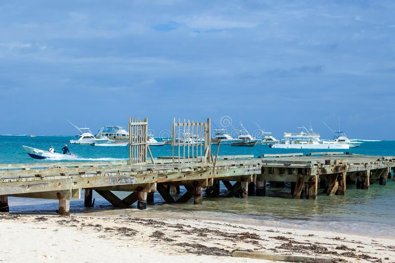 Old wooden dock and modern yachts on a beach in the Dominican Republic royalty free stock photography