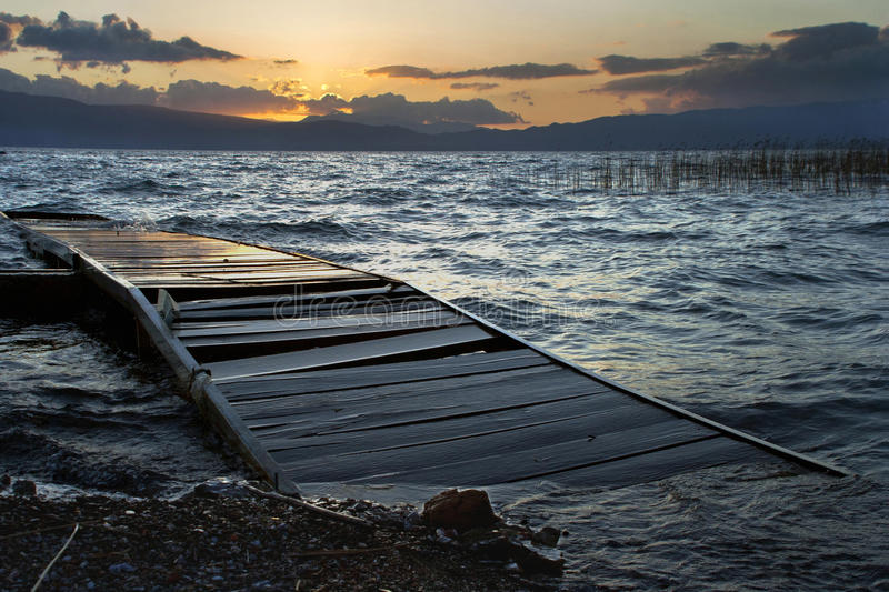 Old wooden dock. On a sunset stock photography