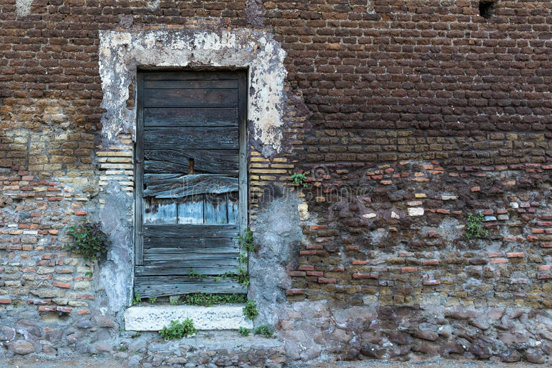 Old wooden door on a brick wall. Right side space stock photos