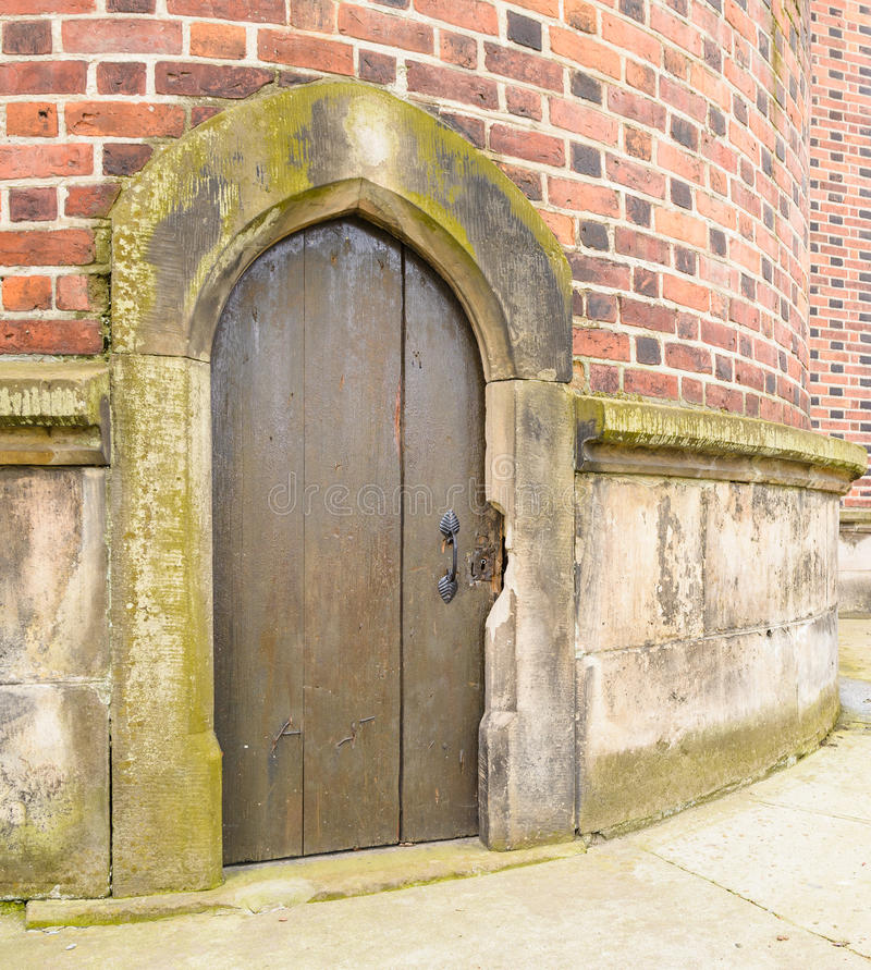Old wooden door in cathedral wall stock photos