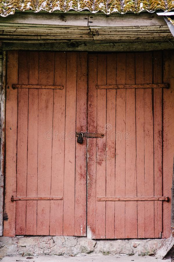 Old wooden door closed on the lock. Peeling paint. House. Barn. stock images