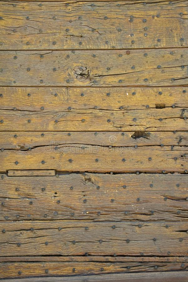 Old wooden door construction full frame background. Full frame close up texture of the planks of an old wooden door royalty free stock image