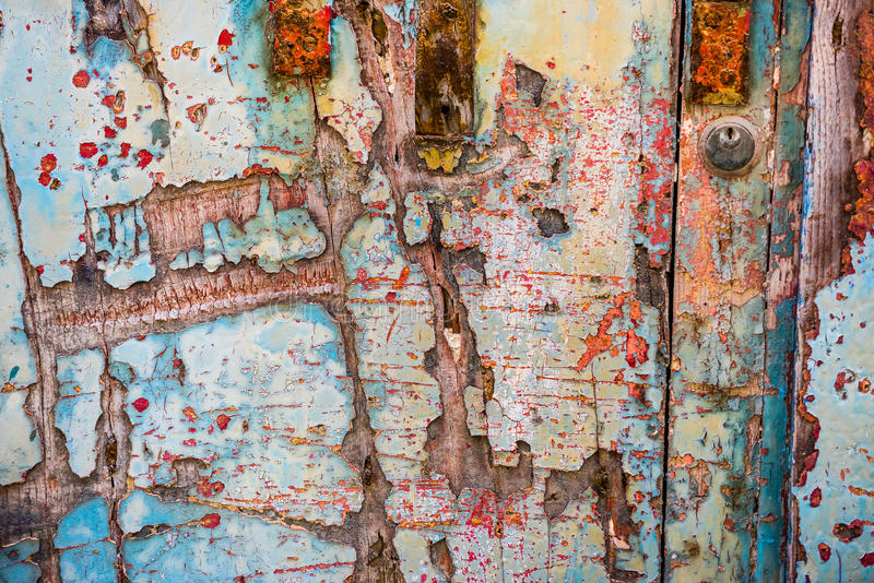 Old wooden door with crumbling paint. Texture of old wooden door with crumbling paint layers royalty free stock photo