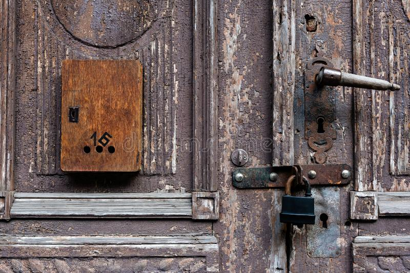 Old wooden door with damaged color and mailbox.  royalty free stock photography