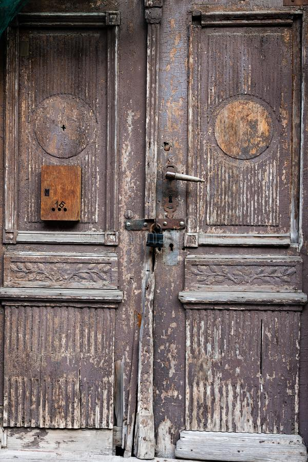 Old wooden door with damaged color and mailbox.  stock photography