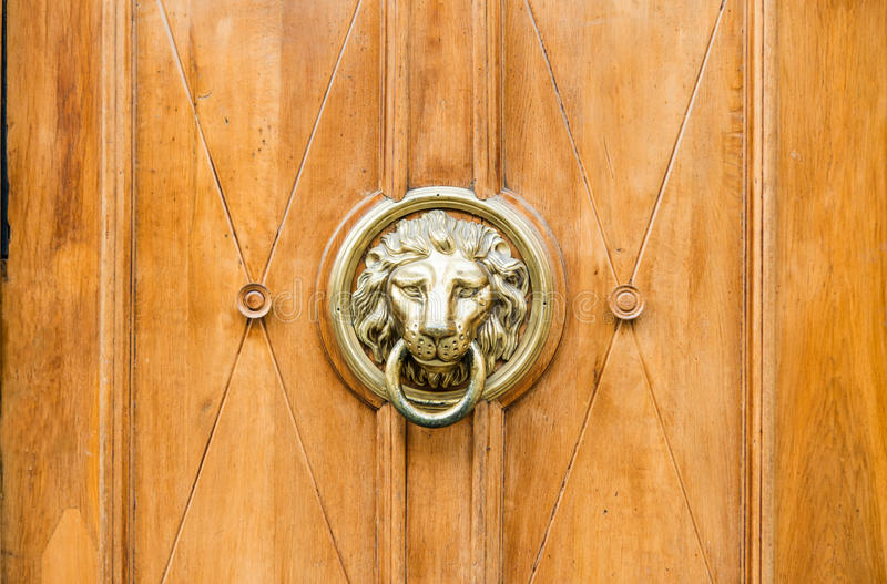 Old wooden door decorated with a lion head as a knocker royalty free stock photos