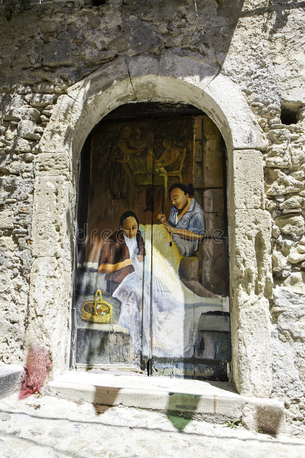 Old wooden door decorated with a painting of two women who embroider in the old city of Amantea. Italy stock image
