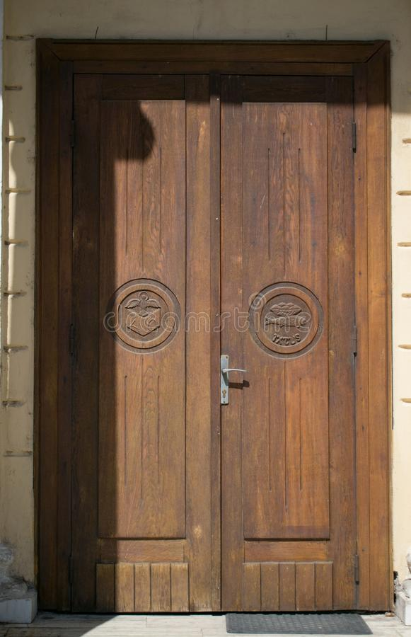 Old wooden door at the entrance to a catholic church. There are different religious symbols on the door.  royalty free stock images