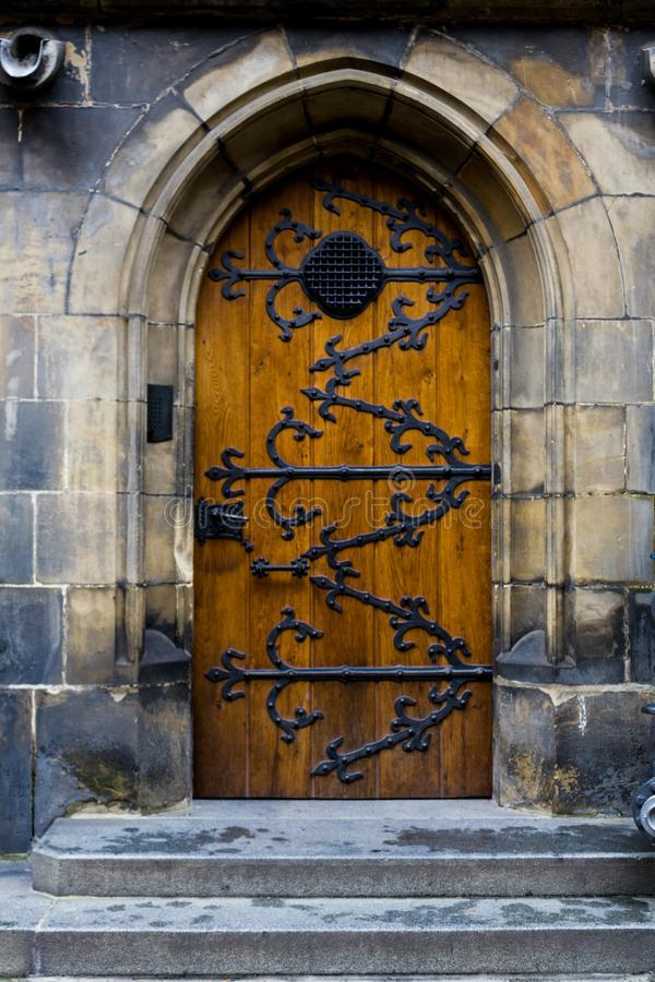 Old wooden door with forged pattern in Gothic style. Prague Castle - Gothic architecture of st. Vitus cathedral back door. Czech royalty free stock photo