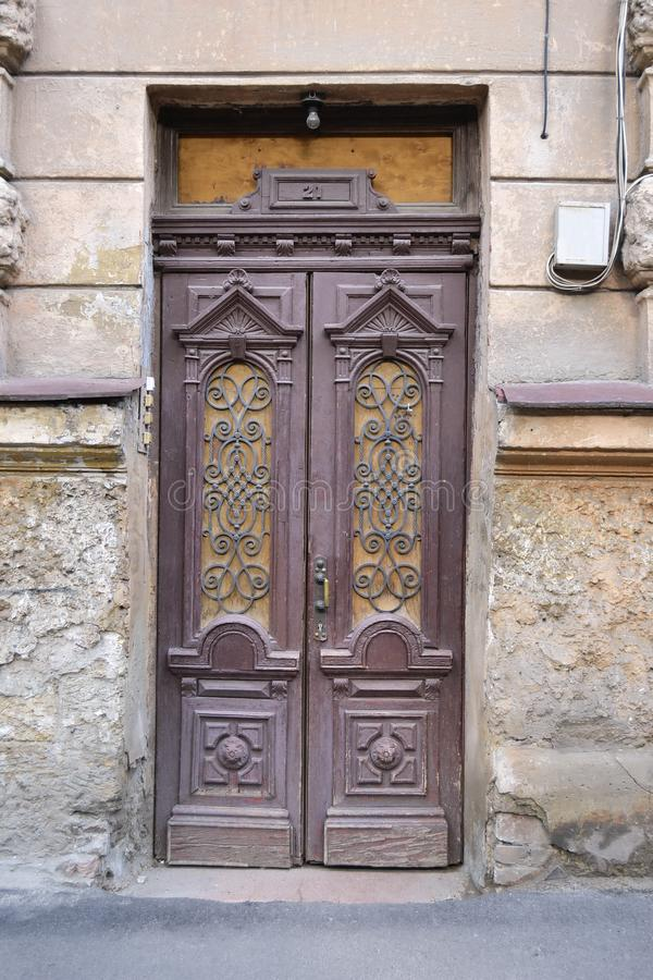 Old wooden door with forged window frames stock photo