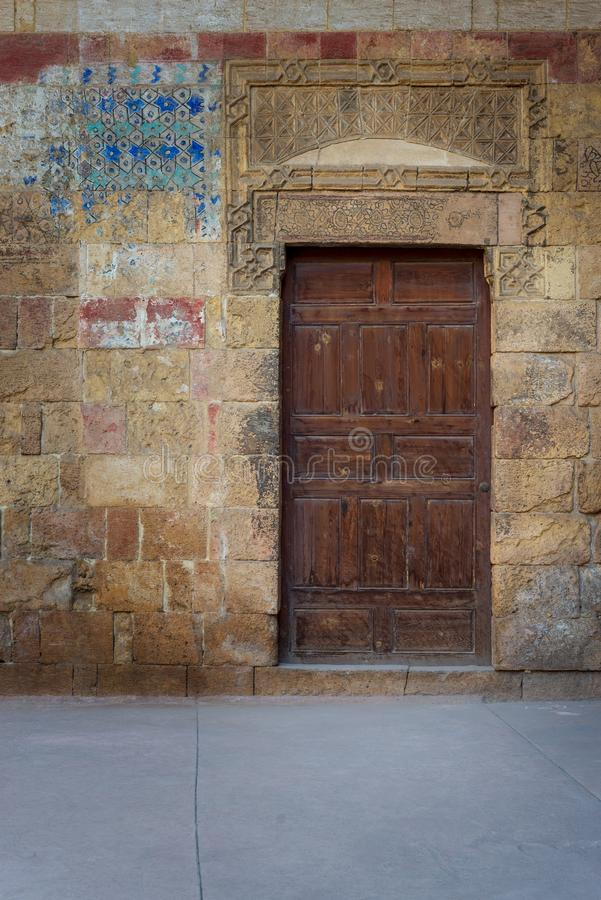 Old wooden door framed by bricks stone wall, Old Cairo, Egypt. Old wooden door framed by bricks stone wall at the courtyard of al Razzaz historic house, Darb al royalty free stock image