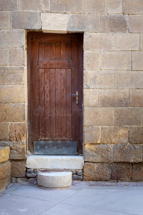 Old wooden door framed by bricks stone wall, Darb al Ahmar district, Old Cairo, Egypt. Old wooden door framed by bricks stone wall at the courtyard of al Razzaz royalty free stock photography