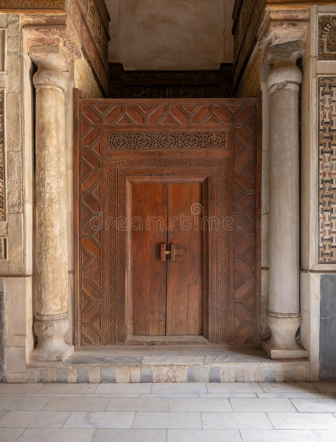 Old wooden door framed by wooden engraved panels decorated with geometric and floral patterns and two carved columns, Cairo, Egypt. Old wooden door framed by royalty free stock photography