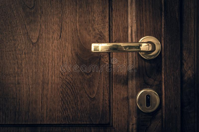 An old wooden door with golden handle sorrounded by black vignette stock photography