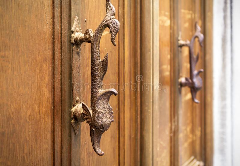 Old wooden door with handles in the form of fish, Venice, Italy. Ornate vintage entrance door. Antique artistic knob close-up. Unique decorative ancient handle stock photos