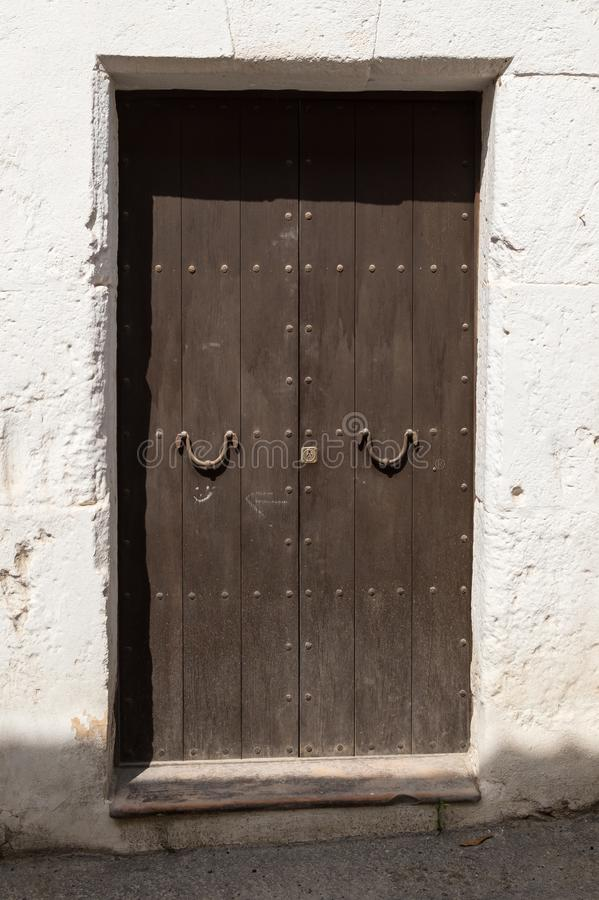 Old wooden door with iron door handles at noon. In direkt sunlight stock images