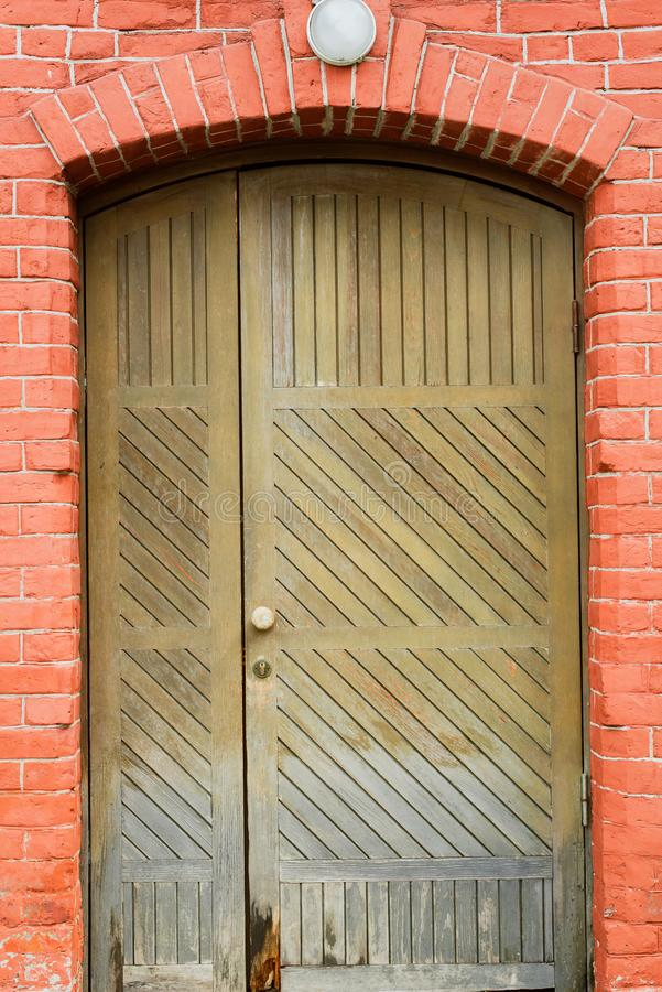 old wooden door with a lantern above it stock photo
