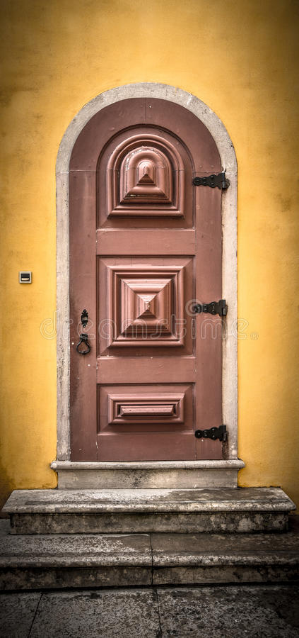 Old wooden door with metal hinges and lock on the yellow wall. T. Oned royalty free stock images
