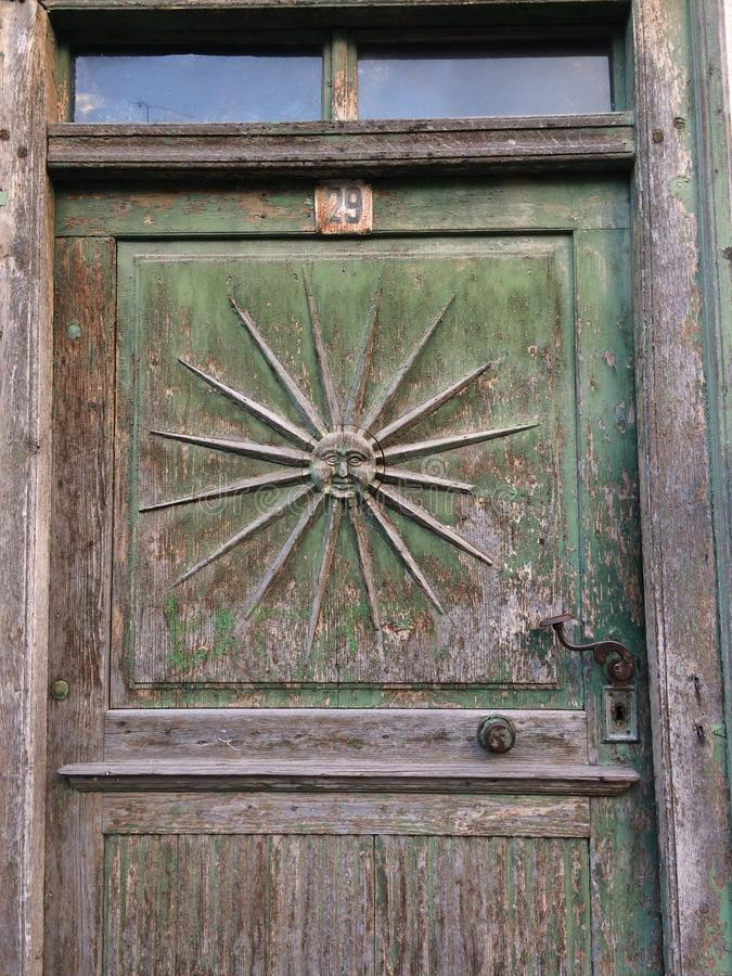 Old door with sun ornament and old wrought iron handle royalty free stock photography