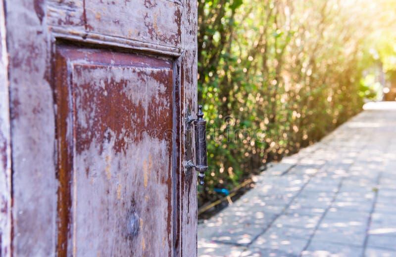 Old wooden door open with old metal door handle. In garden stock photo
