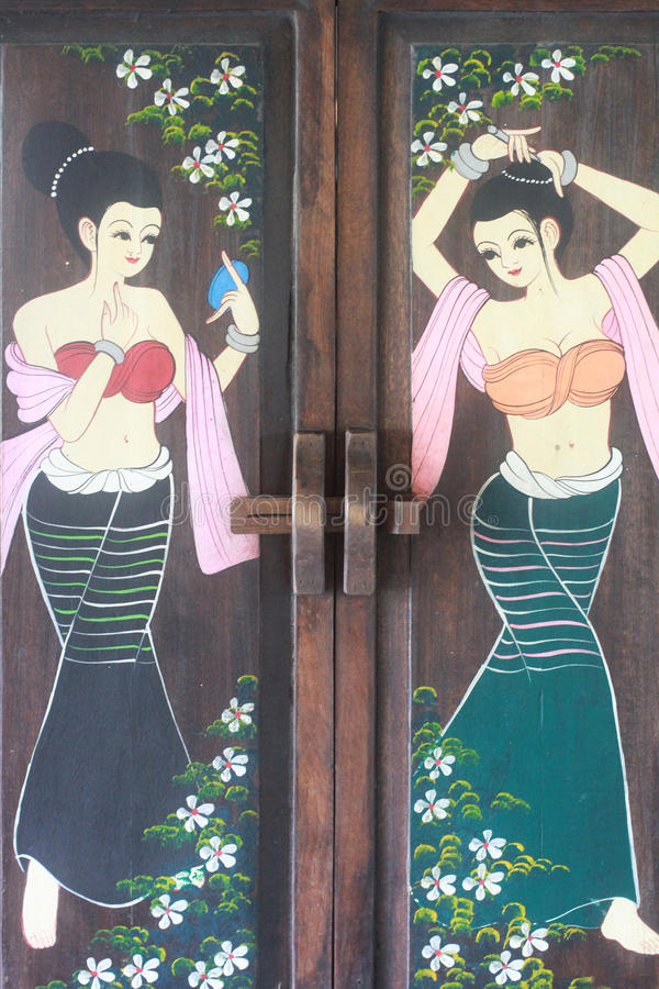 Old wooden door painted with thai style ladies drawing picture, beautiful girl cartoon and flowers. Backgrounds, wallpaper royalty free stock images