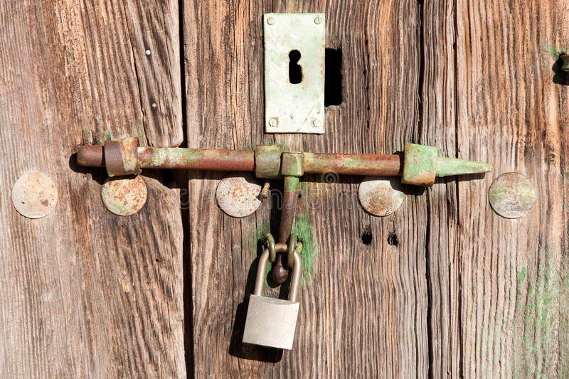 Old wooden door shut with an old rusty royalty free stock image