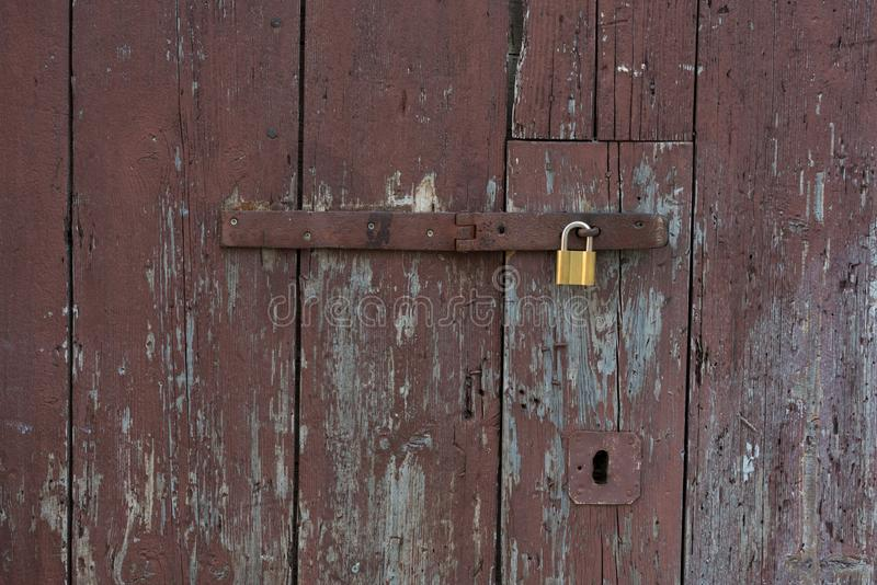Old wooden doors locked with metal yellow lock. New yellow lock on old brown doors stock photo