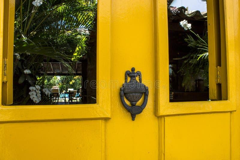 Old wooden doors with an old metal door handle knocker. In Paraty colonial city stock photos