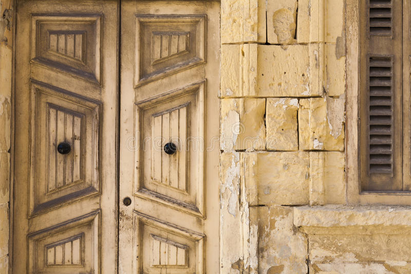 Old wooden doors and stone work on house. Old wooden doors and stone work on traditional built house in Malta stock image