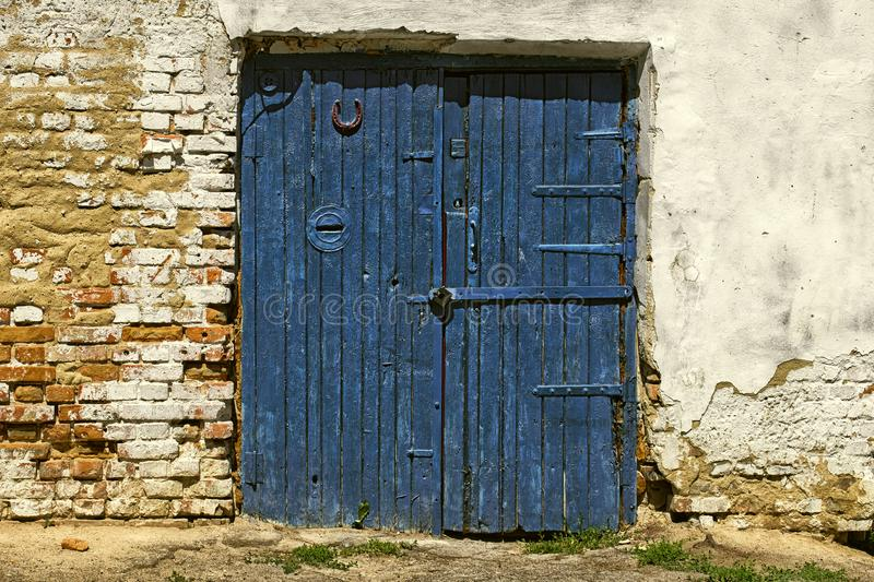 Old wooden double-leaf door with a hidden mailbox and a horseshoe for good luck. An old wooden double door with a hidden mailbox and a horseshoe for good luck stock photo