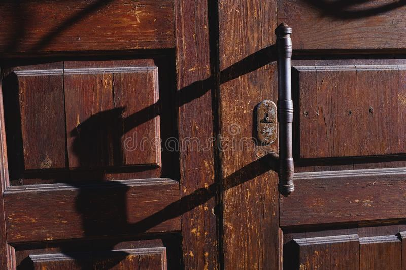 Old wooden entrance door with iron handle. Horizontal shot. Close up royalty free stock image