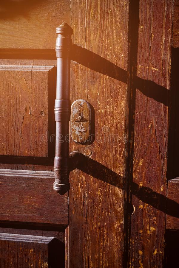 Old wooden entrance door with iron handle. Vertical shot. Close up.  royalty free stock photo