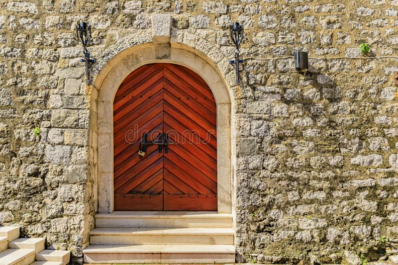 Old wooden entrance gate of the ancient Citadel fortress in Budva Old Town, in Montenegro, Balkans royalty free stock photo