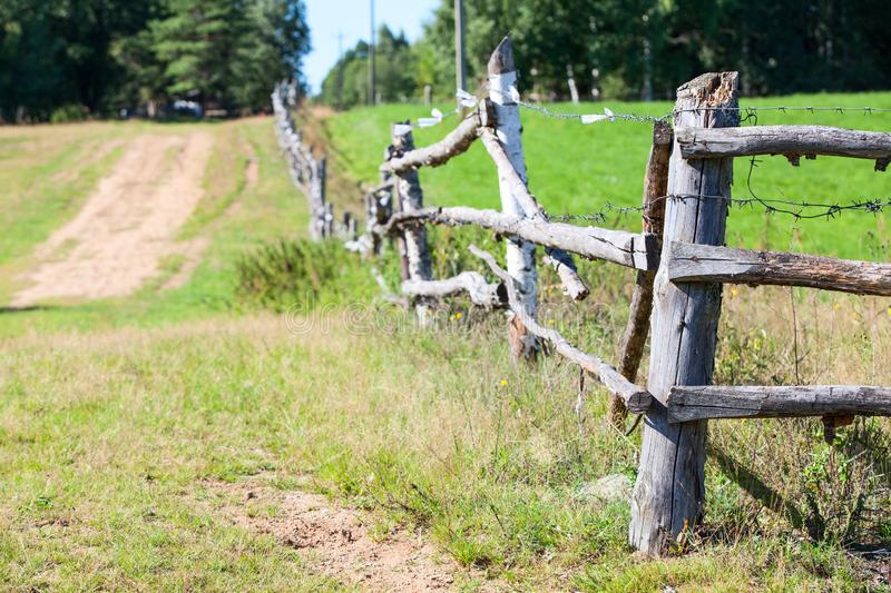 Old wooden fence with barbwire around green meadow near rural road, nobody. Old dilapidated wooden fence with barbwire around green meadow near rural road stock photography