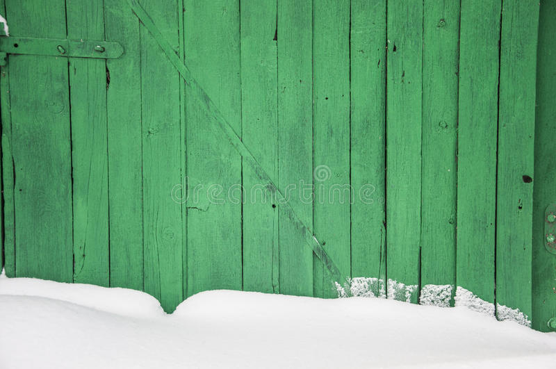 Old wooden fence, covered with snow. Old dark wooden fence in snow royalty free stock photography
