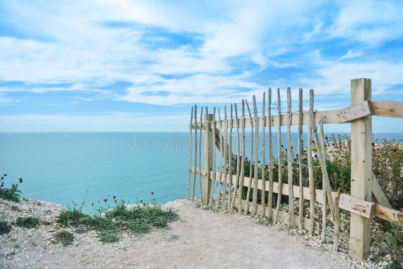 An old wooden fence at the edge of chalk cliffs, coastal erosion stock photography