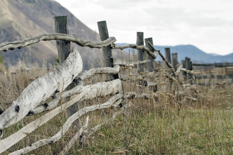 Old wooden fencing on mountain backgruond. Rustic landscape.  stock photos