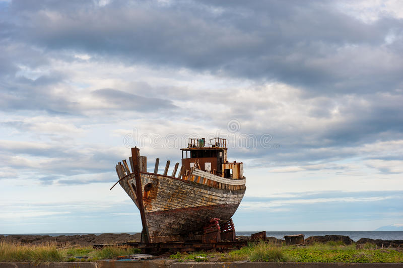 Old wooden fishing boat, Akranes, Iceland. Old wooden fishing boat on the ocean shore, Akranes, Iceland royalty free stock photos