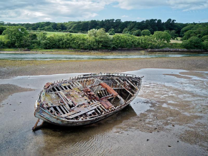 An old wooden fishing boat lay on its side at low tide. royalty free stock images
