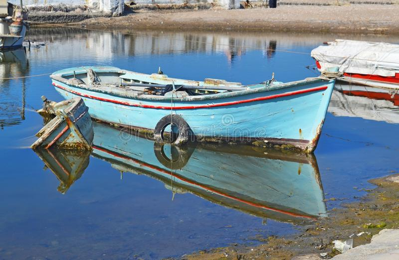 Old wooden fishing boat reflected on water Greece. Old wooden fishing boat reflected on water at a small lake pond Alimos Greece royalty free stock photos